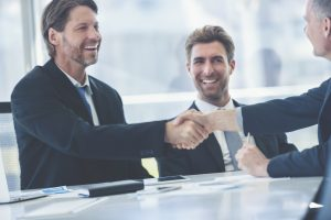 Businessmen shaking hands at the board room table